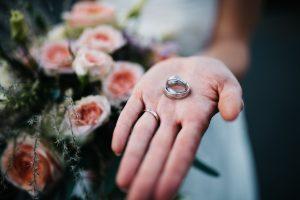 Eheringe auf der Hand und Brautstrauß